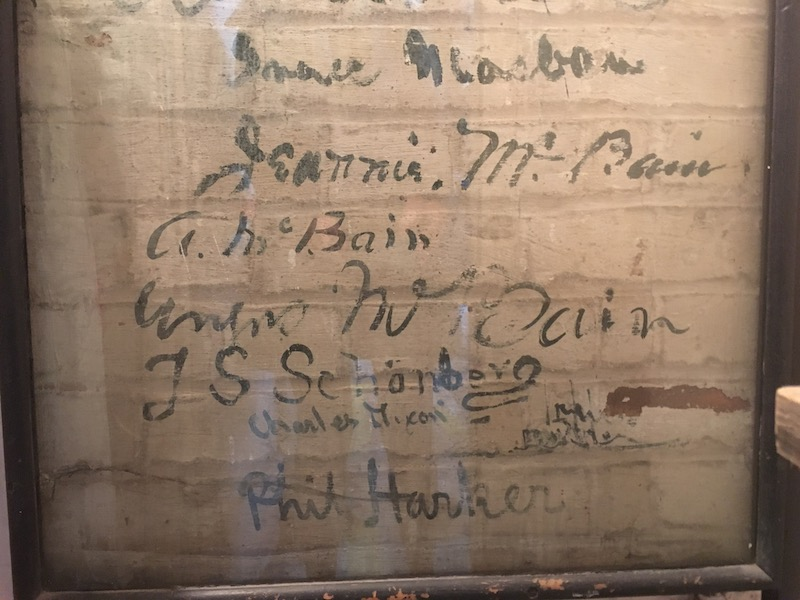 Photograph showing artists' signatures painted on the wall at Joseph Harker's Paint Studio to record the history of the artists who worked at the studio wall (credit: Christina Young)