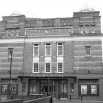 Black and white photograph showing the exterior frontage of the Palace Theatre in Watford (copyright Nigel Cox, used under CC BY-SA 2.0/Desaturated and cropped from original)